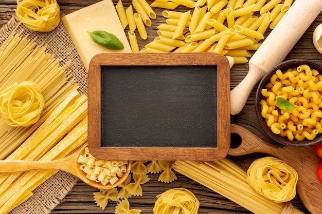 Сырые макароны с макетом на доске