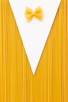 Сырые спагетти фарфалле в форме костюма
