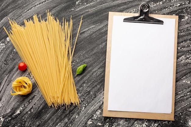 未調理のスパゲッティとタリアテッレ、クリップボードのモックアップ付き