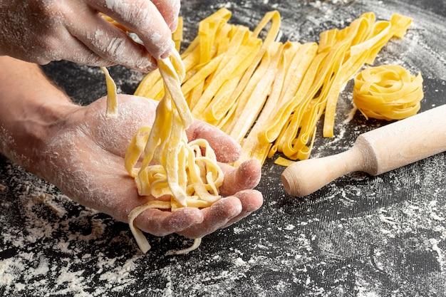Крупным планом шеф-повар делает макароны возле скалки