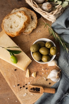 Плоские лежал пармезан, оливки и чеснок на разделочную доску
