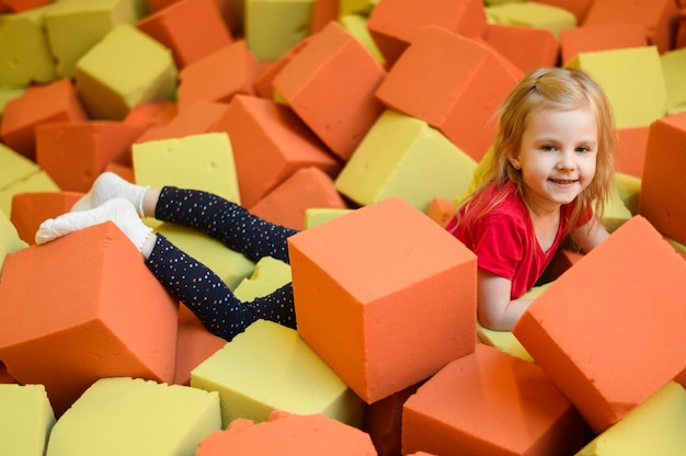 柔らかいブロック遊び場を楽しんで幸せな女の子