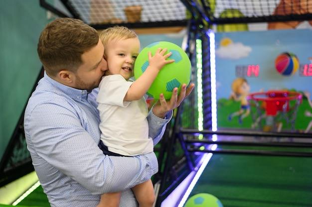 Отец целует сына на детской площадке