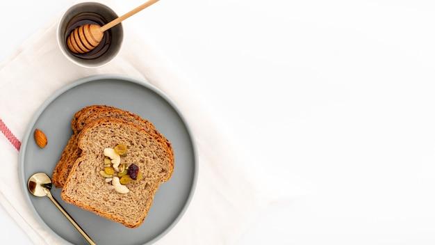 Вкусные ломтики хлеба на тарелке с медом