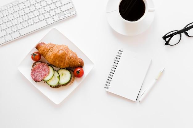 Круассан и бутерброд на тарелку с кофе и блокнотом