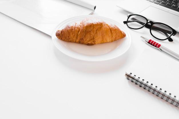 Круассан на тарелке возле ноутбука