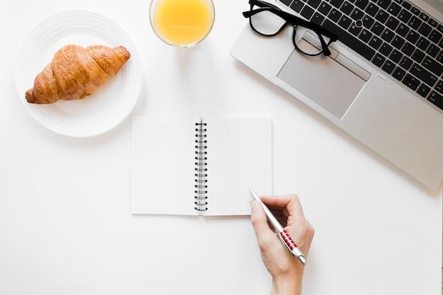 Круассан на тарелку и апельсиновый сок возле ноутбука и ноутбука