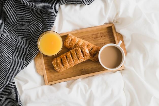 Плоский поднос с выпечкой апельсинового сока и кофе