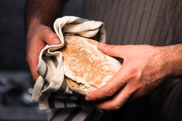 Макро руки держат домашний хлеб