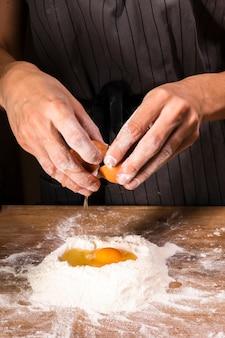 Макро руки разбивают яйцо