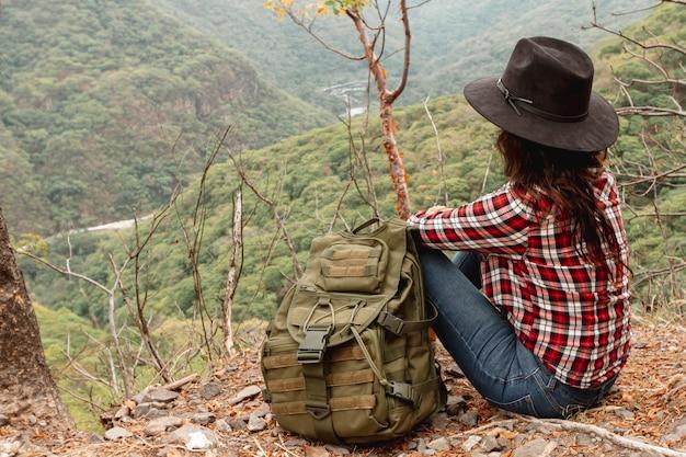 Женщина высокого угла с отдыхом рюкзака