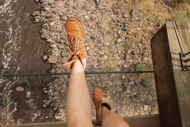 橋の端に座りながら女性の足