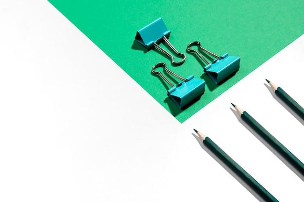 緑色の鉛筆と紙の高いビューのための金属バインダークリップ