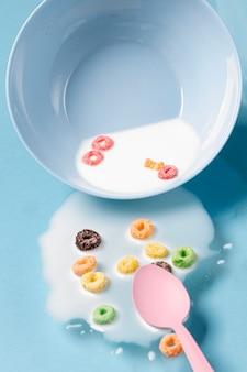 テーブル全体にこぼれたミルクとシリアルとピンクのスプーン