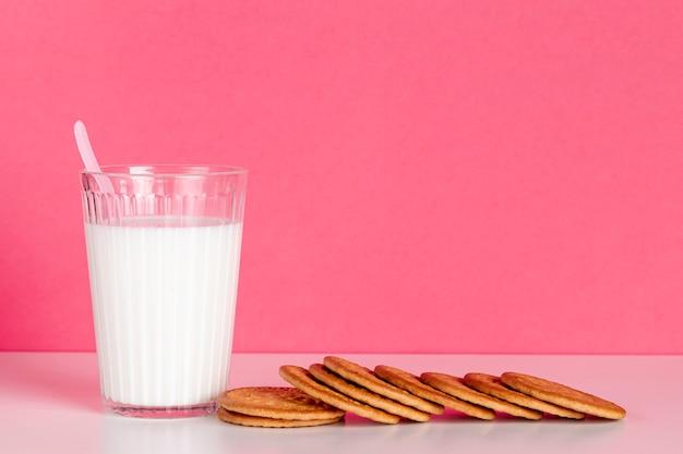 Стакан молока с вкусным печеньем, вид спереди