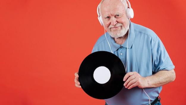 音楽レコードとコピースペースを持つシニア男