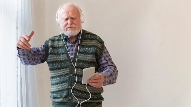 コピースペースで音楽を聴く高齢男性