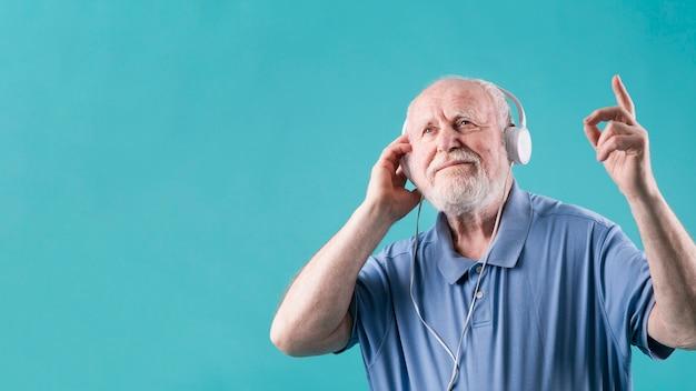 低角度シニア男性の音楽を聴く