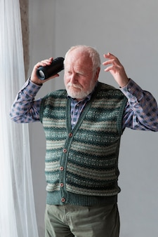 年配の男性がスピーカーで歌を再生