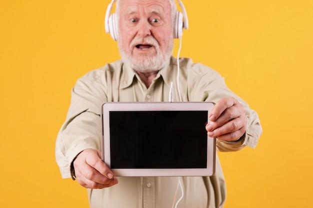 年配の男性がタブレットで音楽を聴く