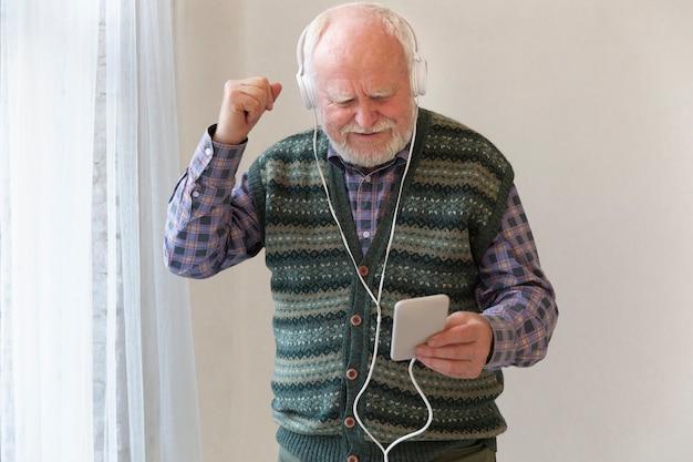 低角度のシニアのスマートフォンで音楽を聴く