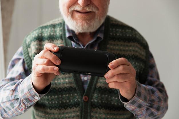 Крупным планом старший играет музыку на мобильном телефоне