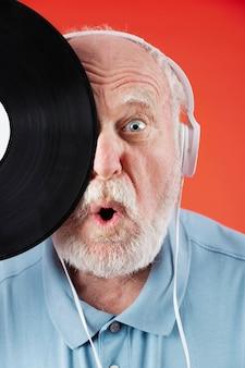 音楽レコードとクローズアップの遊び心のあるシニア