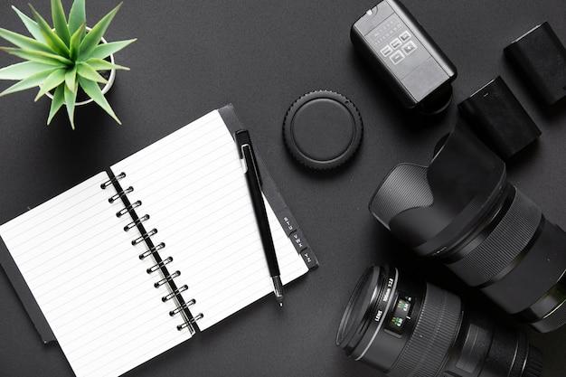 黒の背景にカメラアクセサリーとノートブックのトップビュー