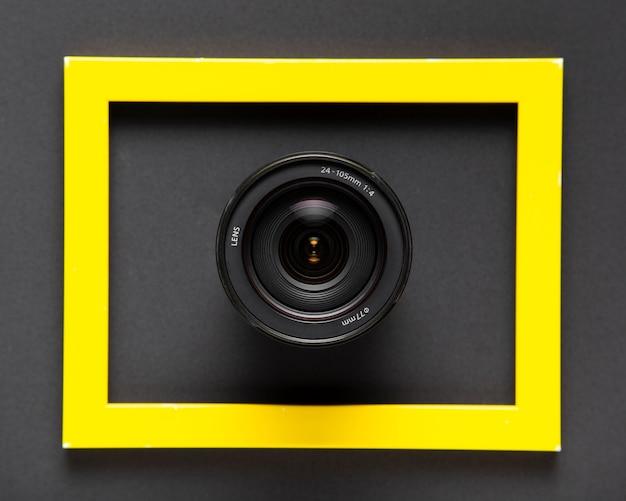 Объективы фотоаппарата внутри желтой рамки на черном фоне