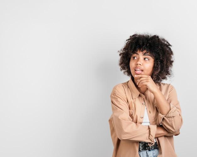 Афро-американская женщина думает и смотрит в сторону