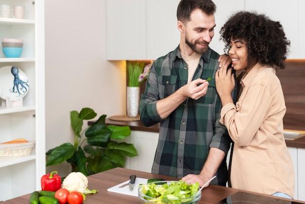 彼女のガールフレンドに野菜のスライスを提供している男