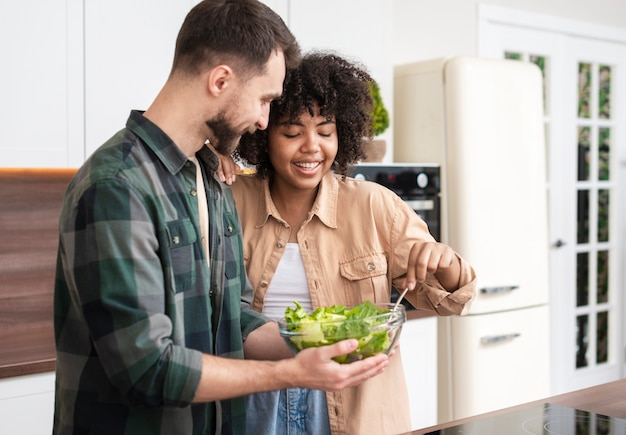 幸せな男と女のサラダを食べる