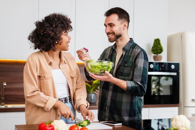 彼女のガールフレンドにサラダを提供している男
