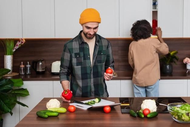 野菜を保持している流行に敏感な若い男