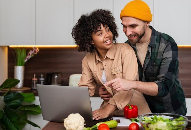 キッチンでラップトップに取り組んでいる若いカップル