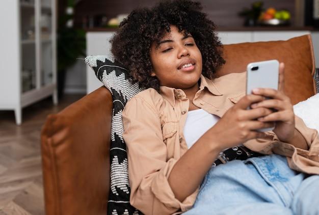 Красивая женщина, отдыхая на диване и глядя на телефон