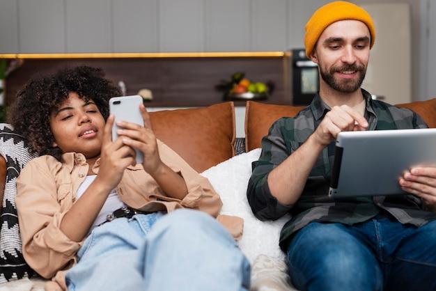 Человек работает на планшете и женщина смотрит на телефон