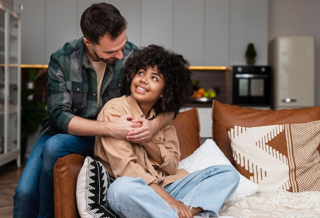 Мужчина обнимает красивая женщина, сидя на диване
