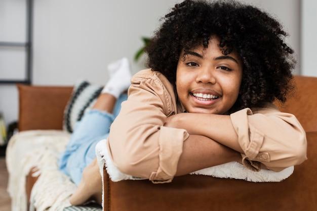 Красивая женщина сидит на диване и смотрит на фотографа