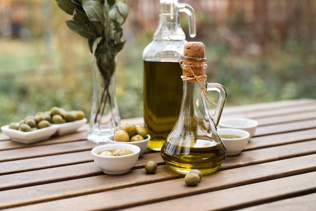 Вид спереди бутылки оливкового масла на столе