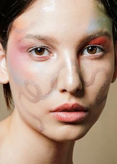 女性の顔に芸術的なペイントのクローズアップ