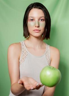 Женщина бросает яблоко во время позирования