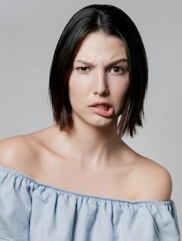 Женщина делает глупое лицо во время позирования