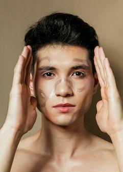 顔の横に手を置く男の正面図