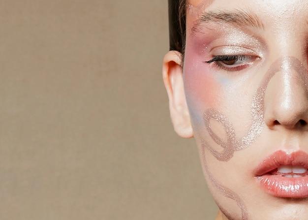 若いモデルのクローズアップの半分の顔