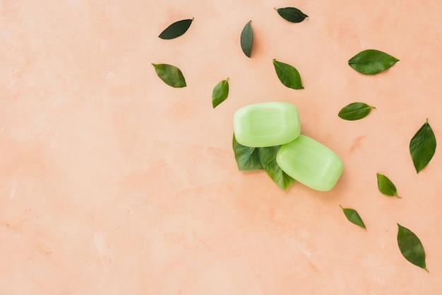 Мыло и листья на оранжевом фоне с копией пространства