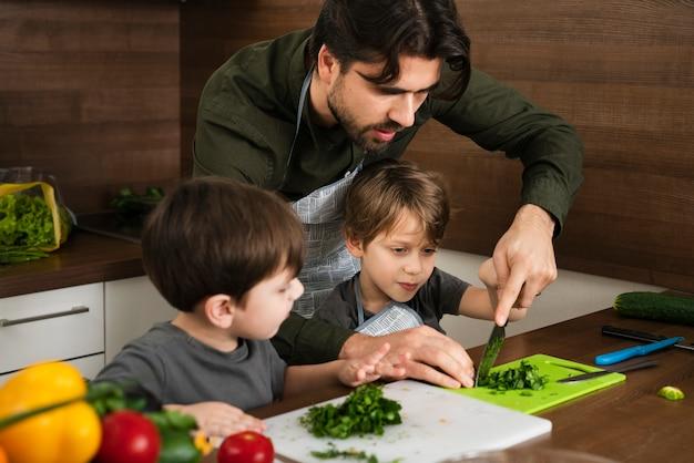 野菜を切ることを息子に教える父