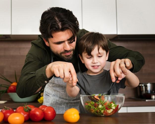 サラダをミックスするお父さんを助ける少年