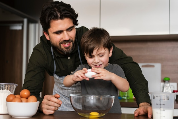 Низкий угол маленький мальчик трещит яйца