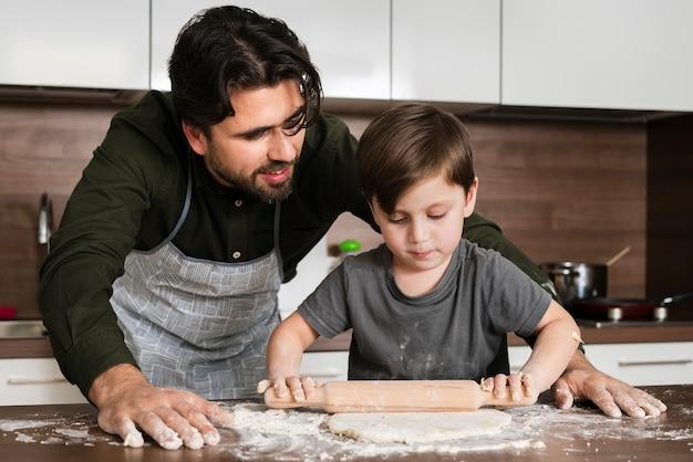 Сын раскатывает тесто под отцом вахты
